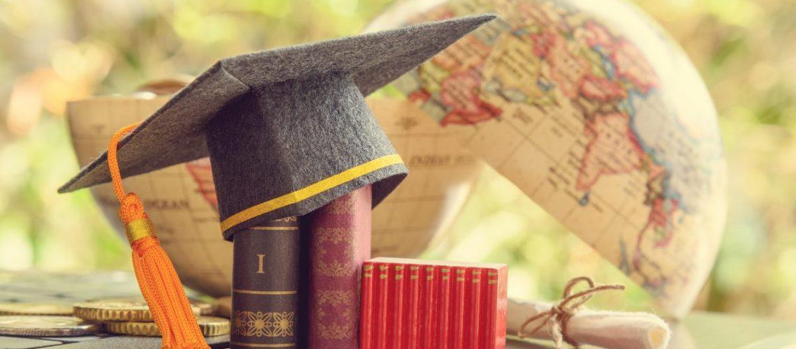 Graduation cap placed on books beside a globe